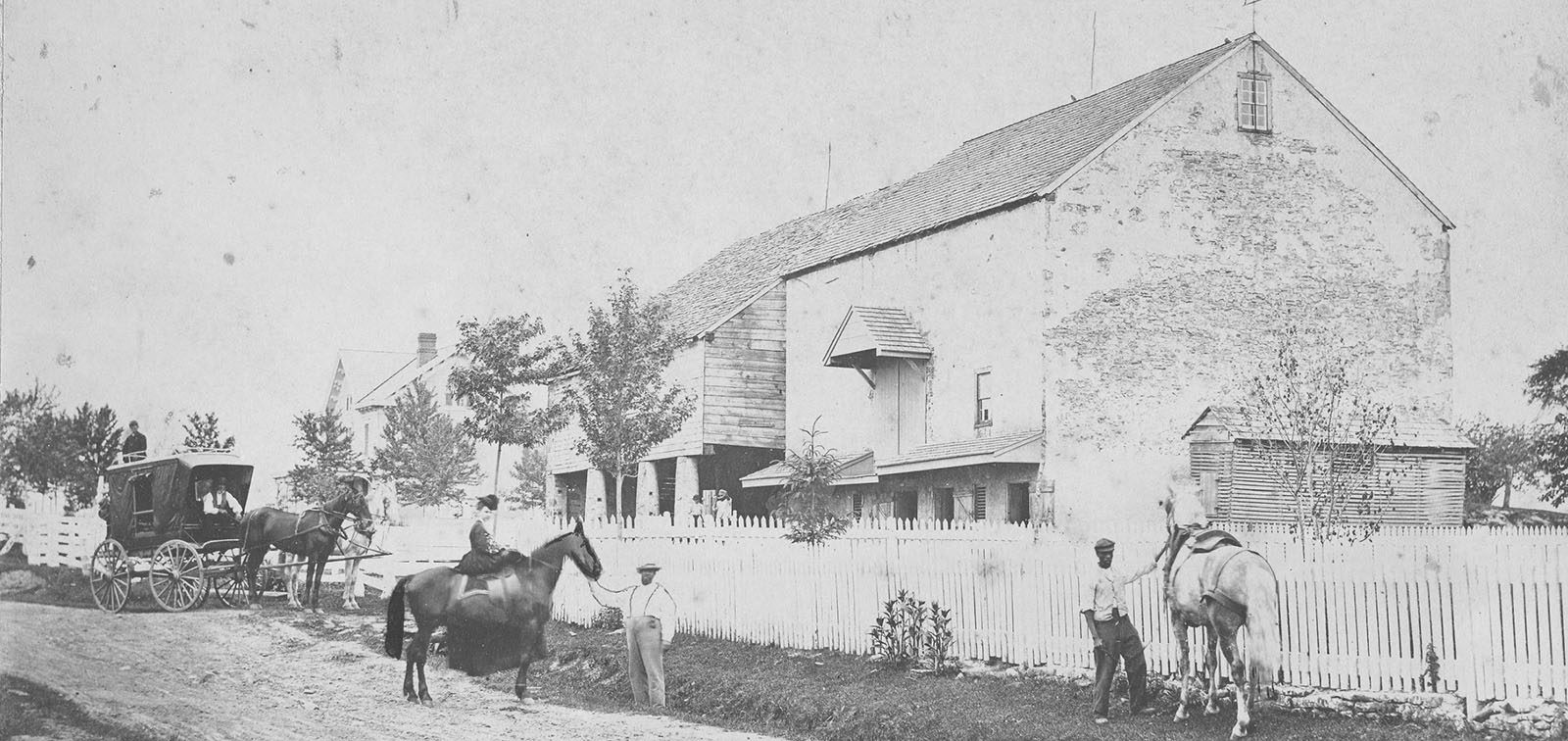 photo of Hannah Davis Saunders on horse back in front of her barn