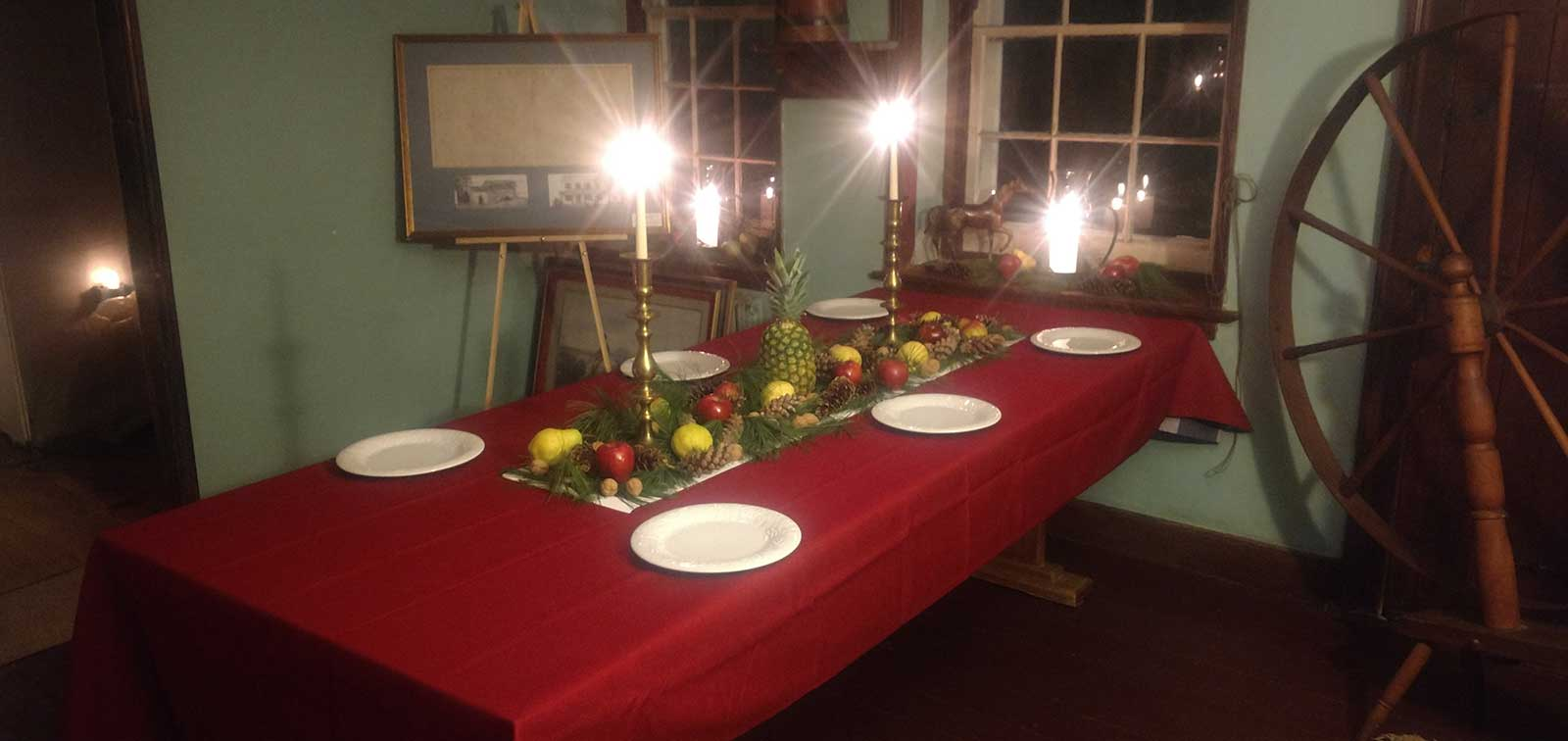photo of table with red table cloth and senter runner with pears, apples and pineapple