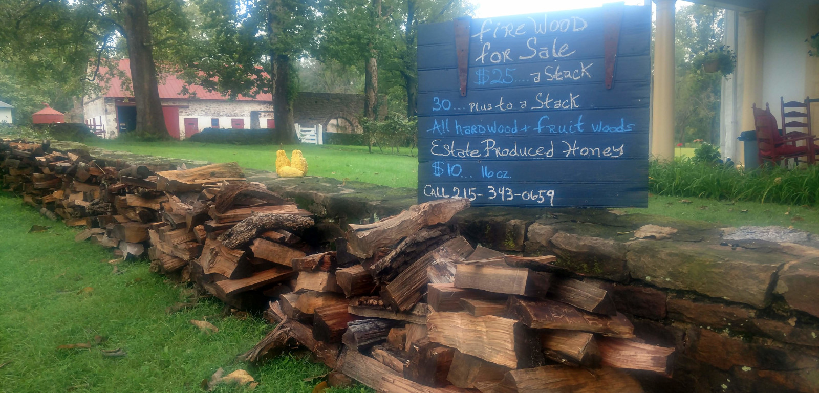 sign selling firewood with stacks of wood against stone wall with barn in distant background