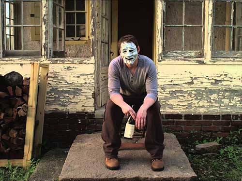 photo of man in mask in front of run down sun room