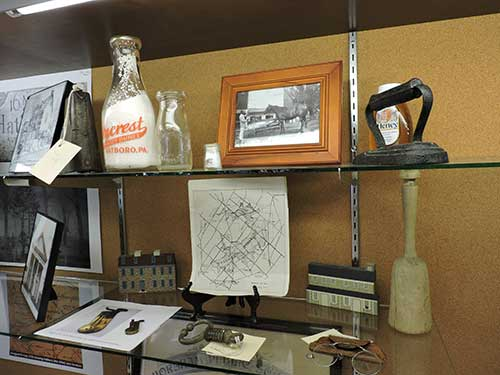 photo of display case showing milk bottle, iron and other artifacts from the Horsham area