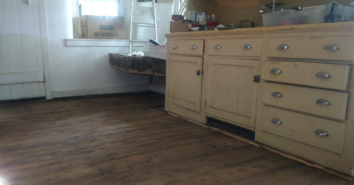 Original pine floor in the 1856 kitchen and 1920s era yello cabinets to right and stone sink in center
