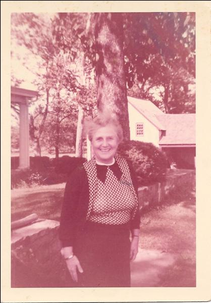 photo of Margaret Strawbridge in front of the house with stone wall and tree behind her
