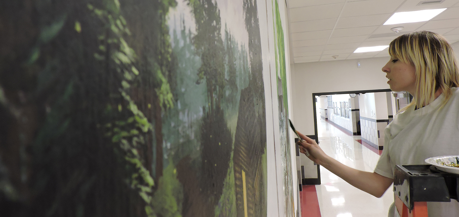 photo of justine musick working onher historical mural at Hallowell Elementary School