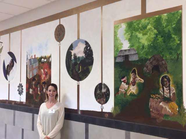 photo of Justine Musick with her historical mural at Hallowell Elementary School