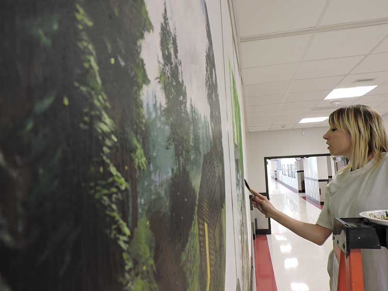 photo of Justine Musick working on Hallowell Elementary Historical Mural